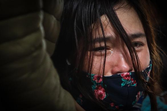 Chị Thiều Thị Phương Nhung - vợ thượng úy Trần Quốc Dũng - bật khóc khi nhìn thấy đoàn xe chở thi thể các cán bộ, chiến sĩ Đoàn kinh tế - quốc phòng 337 tại Hướng Hóa về tới TP Đông Hà (Quảng Trị) vào sáng 19-10 - Ảnh: NGUYỄN KHÁNH